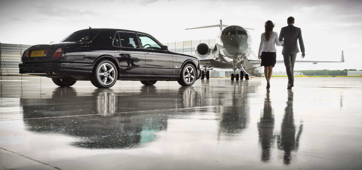 Two people walking towards a private jet