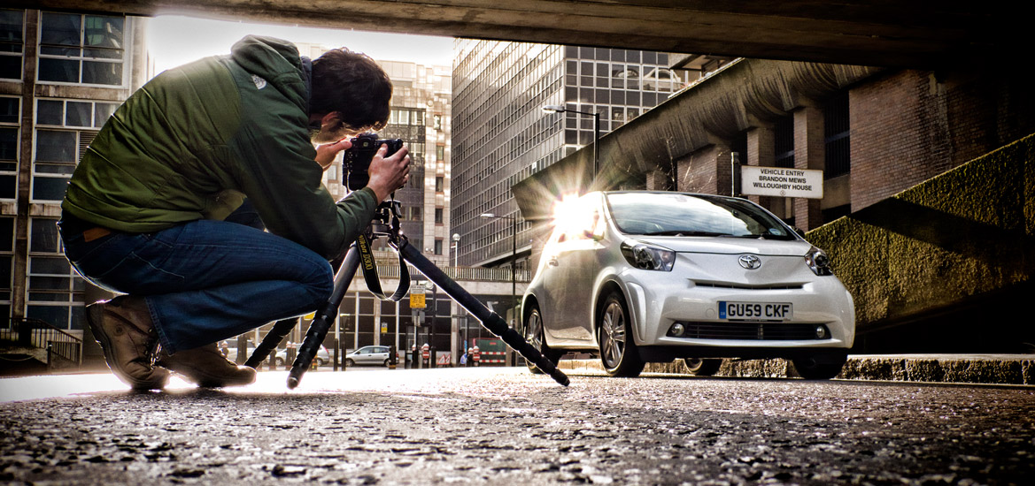 Car photographer using a tripod photographing a car on a street