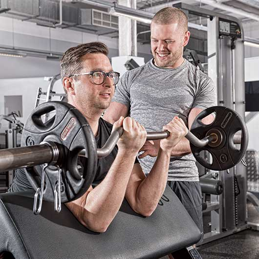 Personal trainer teaching use of weights in an Essex gym
