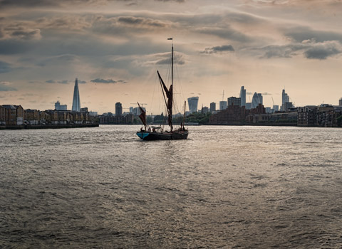 Thames barge on the river sailing towards the centre with the City skyline in the background