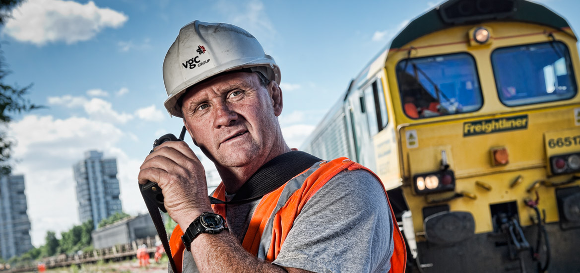 Portrait of a construction worker on a railway with a locomotive in the background